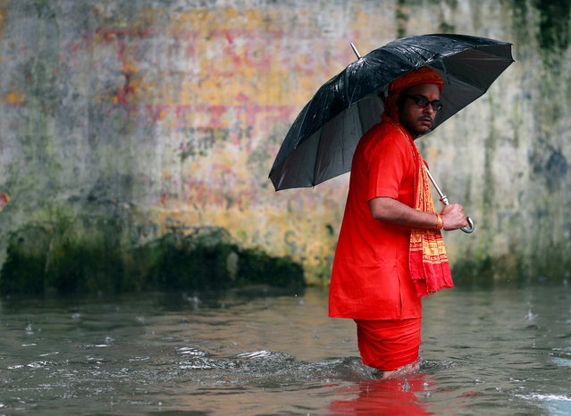 A Hindu priest wades through a waterlogged street during heavy rains in Mumbai, July 8, 2018. (Photo by Danish Siddiqui/Reuters)