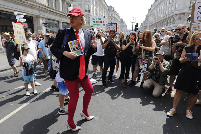 """A man dressed as President Trump poses for a photograph as protesters against the UK visit of US President Donald Trump gather to take part in a march and rally in London on July 13, 2018. US President Donald Trump launched an extraordinary attack on Prime Minister Theresa May's Brexit strategy, plunging the transatlantic """"special relationship"""" to a new low as they prepared to meet Friday on the second day of his tumultuous trip to Britain. (Photo by Tolga Akmen/AFP Photo)"""
