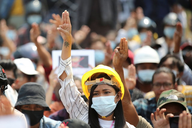 A woman shows a three-finger salute during a protest against the military coup in Naypyitaw, Myanmar, March 8, 2021. (Photo by Reuters/Stringer)