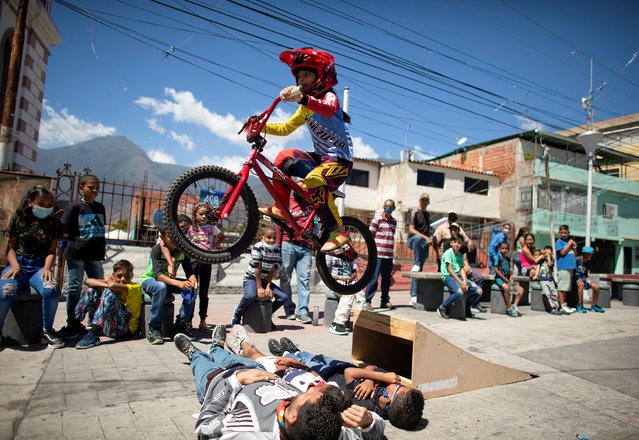 Camila Iachini, 8, performs with her bike during celebrations for the 400th anniversary of the founding of the neighbourhood Petare, in Caracas, Venezuela on February 17, 2021. (Photo by Leonardo Fernandez Viloria/Reuters)