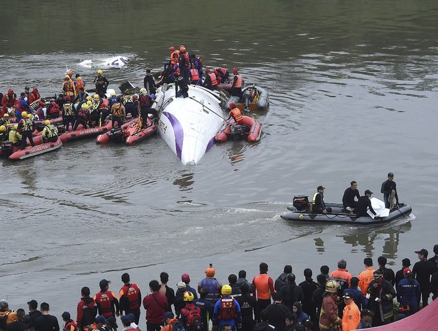 Rescuers remove a body by boat after a TransAsia Airways plane crash landed in a river in New Taipei City February 4, 2015. (Photo by Reuters/Stringer)