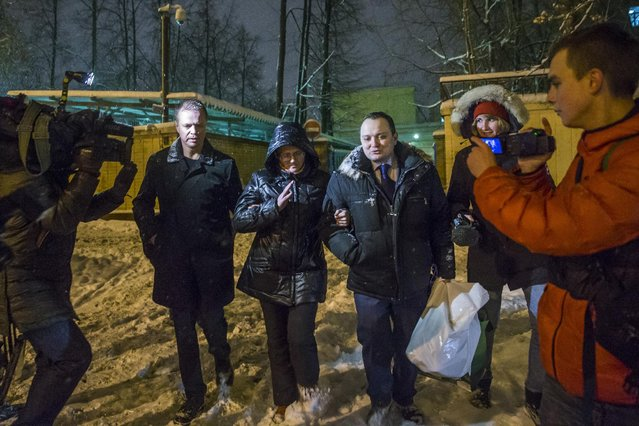 Svetlana Davydova, center, a mother of seven, who lives in the city of Vyazma in western Russia and was arrested last month on treason charges for providing Ukraine with information on Russian troops movements, walks with two unidentified men after she was released for a prison in Moscow, Russia, Tuesday, February 3, 2015. (Photo by Pavel Golovkin/AP Photo)