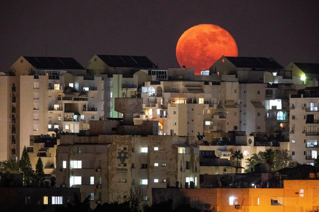 A full moon is seen behind buildings at night in Ashkelon, southern Israel on December 1, 2020. (Photo by Amir Cohen/Reuters)
