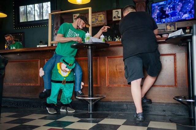 James Paulauski (L) of Carlisle, Massachusetts, orders another drink at Marky's Bar as he celebrates St. Patrick's Day on Bourbon Street after coronavirus disease (COVID-19) restrictions were eased the weekend before, in New Orleans, Louisiana, U.S., March 17, 2021. (Photo by Kathleen Flynn/Reuters)
