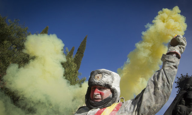 "A reveller covered in flour holds a smoke bomb during the ""Enfarinats"" battle in the southeastern Spanish town of Ibi on December 28, 2015. During this 200-year-old traditional festival participants known as Els Enfarinats (those covered in flour) dress in mock military clothes and stage a mock coup d'etat as they battle using flour, eggs and firecrackers outside the city town hall as part of the celebrations of the Day of the Innocents. (Photo by Jaime Reina/AFP Photo)"