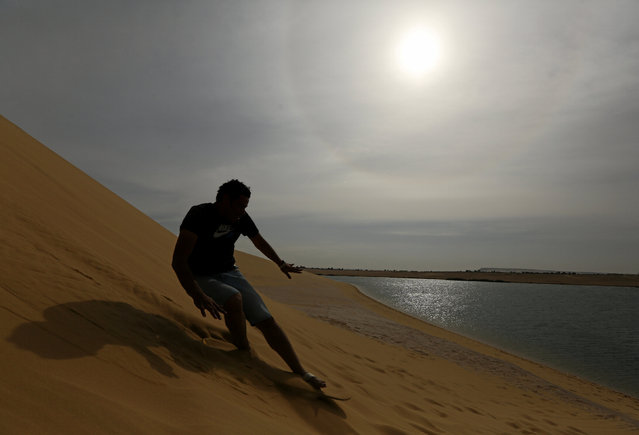 A man sandboards down the mountain in Wadi el-Rayan Fayoum, Egypt, November 18, 2016. (Photo by Mohamed Abd El Ghany/Reuters)