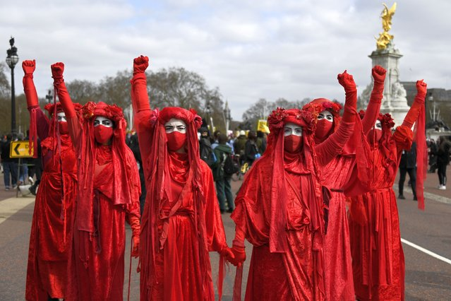 """Extinction Rebellion activists perform during a """"Kill the Bill"""" protest in London, Saturday, April 3, 2021. (Photo by Alberto Pezzali/AP Photo)"""
