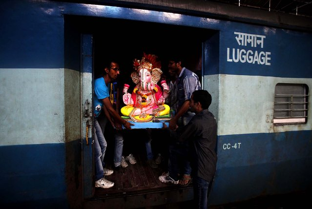 A clay idol of the Hindu god Ganesh is carried onto a passenger train before being transported to a place of worship in Mumbai, on September 1, 2013. Ganesh Chaturthi, celebrated as the birthday of Lord Ganesha, begins September 9. The idols will be immersed in bodies of water at the end of the festival. (Photo by Rafiq Maqbool/Associated Press)