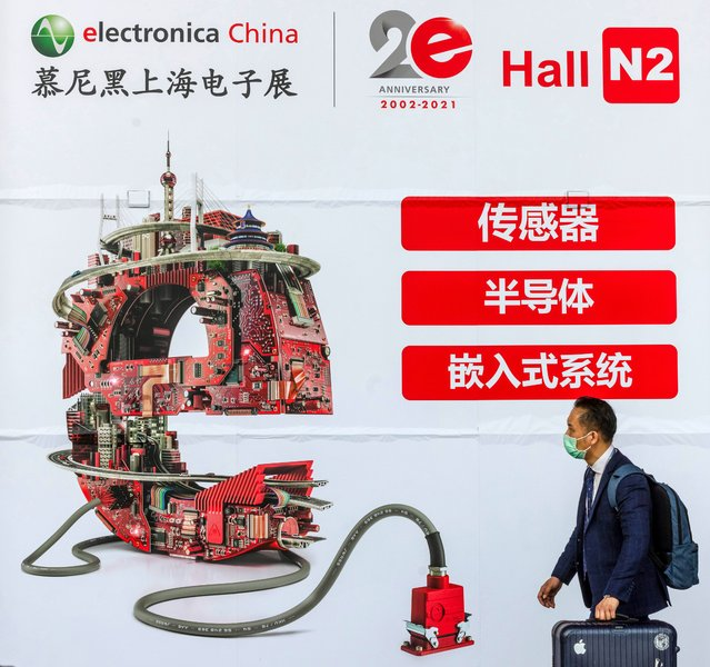 A visitor walks in front of the advertisement on the Electronica China Expo in Shanghai, China, 16 April 2021. Founded in 2002, electronica China is now one of the leading platforms for innovative electronics manufacturing and it's held from 14-16 of April 2021, with over 1,300 exhibitors worldwide. (Photo by Alex Plavevski/EPA/EFE)