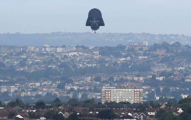 A balloon shaped as the head of fictional Star Wars film character Darth Vader is seen flying at the annual Bristol hot air balloon festival in Bristol, Britain, August 8, 2019. A huge Darth Vader mask balloon took to the skies over the western English port of Bristol on Thursday as the city's annual balloon festival began. (Photo by Toby Melville/Reuters)