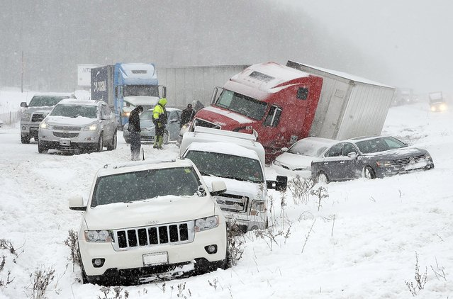 Numerous vehicles rest in a ditch along the shoulder of Interstate 90 after they were involved in a crash that closed the eastbound lanes, Wednesday, January 13, 2016, in Harborcreek Township near Erie, Pa. About 25 vehicles were involved in the weather-related accident, which had multiple lanes of the interstate closed for more than five hours. (Photo by Greg Wohlford/Erie Times-News via AP Photo)