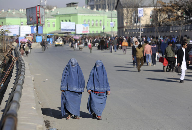 In this Monday, December 5, 2016 photo, Afghan women walk on a street in Kabul, Afghanistan. Afghans are increasingly uncertain about their future, less confident in their government and more pessimistic than before on issues such as security, corruption, and rising unemployment, according to the annual survey by the San Francisco-based Asia Foundation released on Wednesday, Dec. 7, 2016. (Photo by Rahmat Gul/AP Photo)