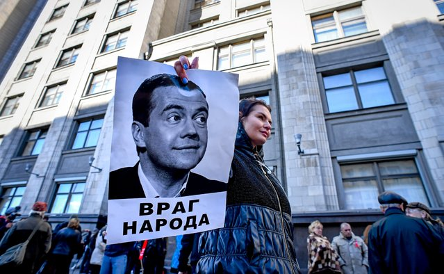 """A protester holds a picture of Russian Prime Minister Dmitry Medvedev bearing an inscription readin """"An enemy of people"""" during a rally against the pension reform in front of the State Duma, the lower house of parliament, in Moscow on September 26, 2018. The Russian parliament on Wednesday unanimously approved President Vladimir Putin's amendments of a hugely unpopular pension reform that has led to a rare outburst of public anger in the country. (Photo by Yuri Kadobnov/AFP Photo)"""