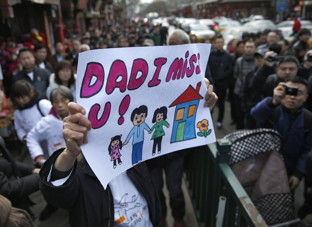A family member of a passenger onboard the missing Malaysia Airlines flight MH370, holds a sign outside Yonghegong Lama Temple after a gathering of family members of the missing passengers in Beijing March 8, 2015. Prime Minister Najib Razak said on Sunday Malaysia remains committed to the search for the missing MH370 jetliner a year after it vanished without trace and he is hopeful it will be found.
