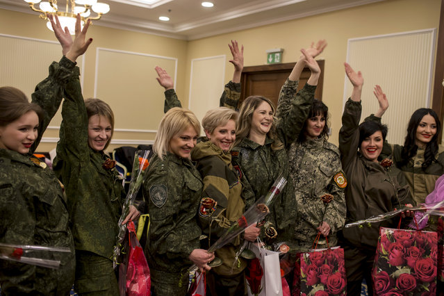 Female soldiers of the self-proclaimed Donetsk People's Republic wave backstage during a beauty pageant to mark International Women's Day in Donetsk, March 7, 2015. (Photo by Marko Djurica/Reuters)