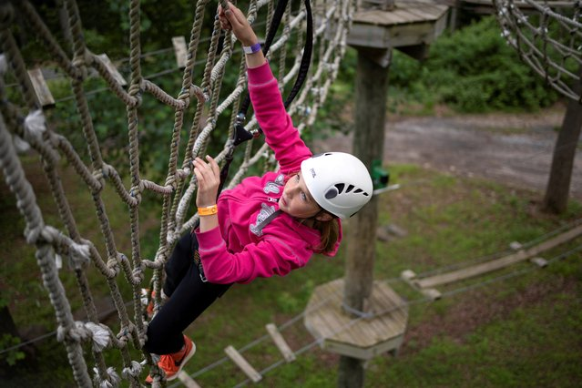 A girl climbs the aerial ropes course at Harpers Ferry Adventure Center for Memorial Day weekend in Hillsboro, Virginia, U.S., May 30, 2021. (Photo by Hannah Beier/Reuters)