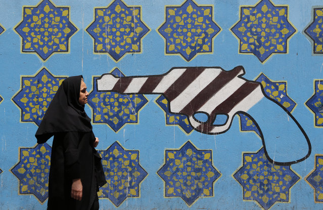"""An Iranian woman walks past a mural depicting a gun painted on the wall of the former US embassy in the capital Tehran on August 7, 2018. US President Donald Trump warned countries against doing business with Iran today as he hailed the """"most biting sanctions ever imposed"""", triggering a mix of anger, fear and defiance in Tehran. (Photo by Atta Kenare/AFP Photo)"""