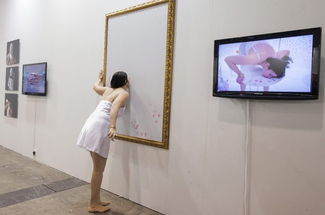 Turkish artist Nezaket Ekici performs a live art performance entitled 'Emotion in Motion' on the first day of Art Basel 2015, Hong Kong, China, 13 March 2015. Art Basel 2015 features 233 galleries from 37 countries and territories. (Photo by Alex Hofford/EPA)