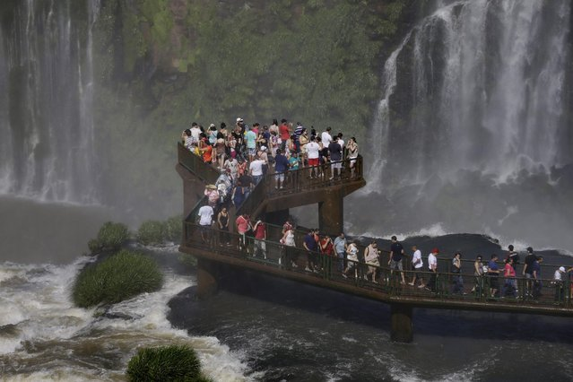 In this photo taken Sunday, March 15, 2015, tourists stand on a platform to get a better view of Iguazu Falls, in Foz do Iguazu, Brazil. Iguazu Falls, on the border of Argentina and Brazil, is part of the Guarani Aquifer, one of the world's major underground reserves of fresh water. (Photo by Jorge Saenz/AP Photo)