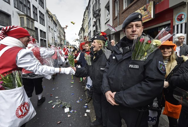 Police get flowers by revelers while they secure the traditional carnival parade in Cologne, western Germany, Monday, February 8, 2016. Many carnival parades in Germany were cancelled because of stormy weather. The foolish street spectacle in Cologne, normally watched by hundreds of thousands of people, is the highlight in Germany's carnival season on Rose Monday. (Photo by Martin Meissner/AP Photo)