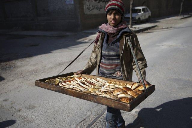A boy sells pastries along a street in the Douma neighbourhood of Damascus, Syria February 9, 2016. (Photo by Bassam Khabieh/Reuters)
