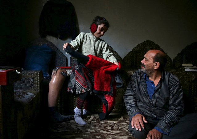 Shahrour, 54, looks at his daughter Hadeel, 10, inside their home in the besieged town of Arbeen, in the Damascus suburbs, Syria February 6, 2016. (Photo by Bassam Khabieh/Reuters)