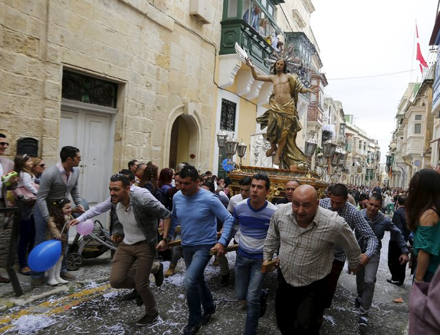 Worshippers run while carrying a statue of the Risen Christ as confetti streams down during an Easter Sunday procession in Cospicua, outside Valletta April 5, 2015. (Photo by Darrin Zammit Lupi/Reuters)