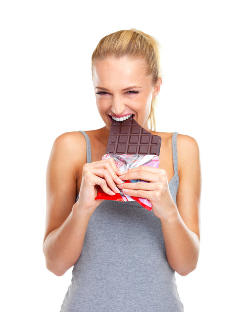 Eager young woman biting into a big slab of chocolate. (Photo by Jacob Wackerhausen/Getty Images)