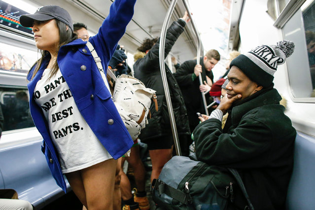 "A woman without pants travels in the subway during the ""No Pants Subway Ride"" in New York, on January 8, 2017. (Photo by Kena Betancur/AFP Photo)"