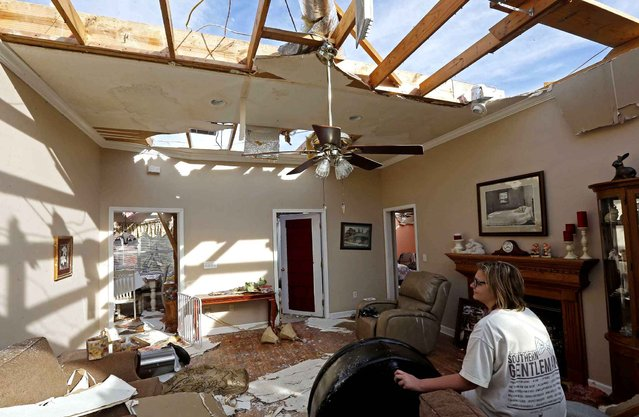 Olivia Grubbs sits in the living room of what remains of the home of her grandparents Vernon and Regina Cavin in Stronghope, Miss., Tuesday, February 16, 2016, following Monday's storm system that brought destructive winds to areas of central and south Mississippi. Several homes and businesses, including this one were severely damaged or destroyed. (Photo by Rogelio V. Solis/AP Photo)