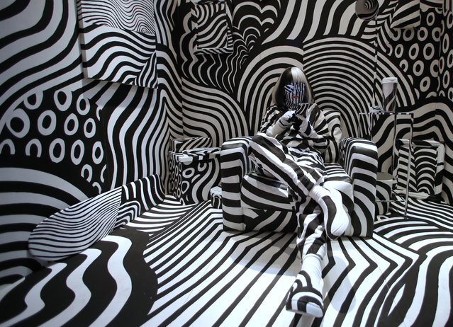"""Model feebee poses as part of art installation """"Dazzle room"""" made by artist Shigeki Matsuyama at Room 32 fashion and design exhibition in Tokyo, Friday, February 19, 2016. Matsuyama's installation features a strong contrast of black and white, which he learned from dazzle camouflage used mainly in World War I, in Tokyo, Friday, Feb. 19, 2016. (Photo by Shuji Kajiyama/AP Photo)"""