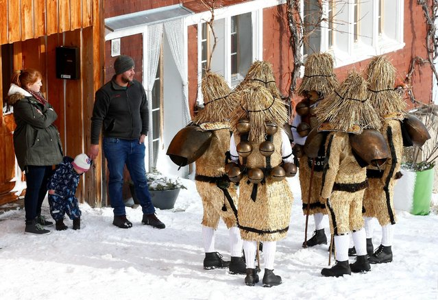 """Residents watch men dressed as """"Chlaeuse"""", figures that scare away evil spirits, carry round bells and cowbells as they perform during the traditional """"Sylvesterchlausen"""" near the northeastern village of Urnaesch, Switzerland January 13, 2017. (Photo by Arnd Wiegmann/Reuters)"""