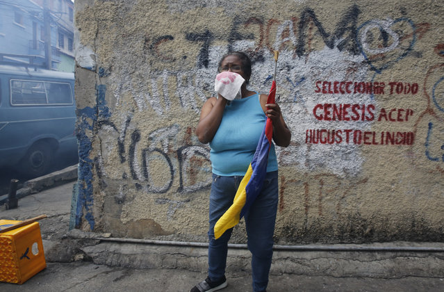 An anti-government protester affected by tear gas, fired by security forces, holds a Venezuelan flag during a show of support for an apparent mutiny by a national guard unit in the Cotiza neighborhood of Caracas, Venezuela, Monday, January 21, 2019. (Photo by Ariana Cubillos/AP Photo)