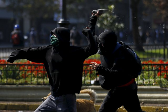 Protesters throw stones against riot police during a demonstration against the government to demand changes in the education system at Santiago, April 16, 2015. (Photo by Ivan Alvarado/Reuters)