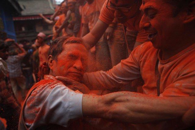 A Nepalese man smears vermillion powder on his friend during Sindur Jatra festival in Thimi, outskirts of Kathmandu, Nepal, Wednesday, April 15, 2015. (Photo by Niranjan Shrestha/AP Photo)