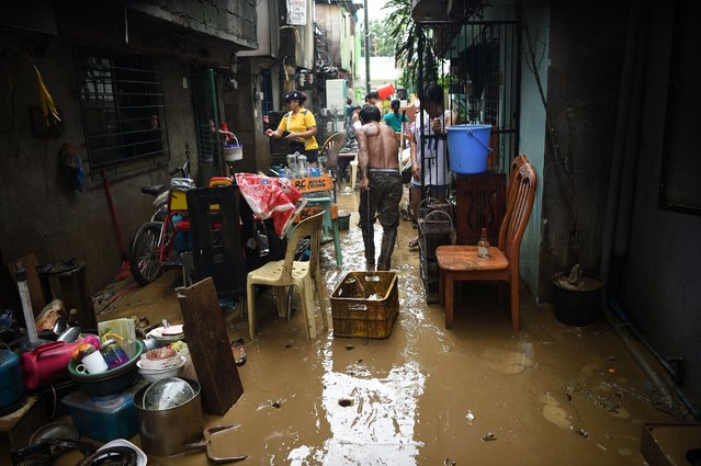 Residents clean their mud-filled homes after flooding brought about by heavy downpour due to exiting Tropical storm Yagi, submerged their homes in Marikina City, suburban Manila on August 12, 2018. The latest storm brought misery to many, with 20,000 residents fleeing the riverside district of Marikina in the national capital region, where floods swept away cars, authorities said. (Photo by Ted Aljibe/AFP Photo)