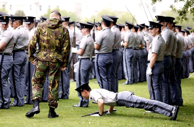 Citadel cadet Daniel Kim, a junior from Fairfax, V.A., does disciplinarian push-ups during practice for the schools weekly parade on the grounds of Summerall Field on the campus of The Citadel in Charleston, S.C., Thursday, April 16, 2015. The Citadel's parade is usually every Friday at 3:45 and is free to attend and open to the public. (Photo by Mic Smith/AP Photo)