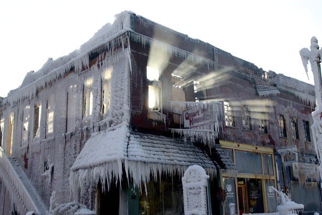Sunlight streams through the windows of a building which caught on fire in Plattsmouth, Neb., Friday, January 3, 2014, and the water sprayed on it by fire fighters froze. Much of the American northeast and the midwest are suffering from sub-freezing temperatures. (Photo by Nati Harnik/AP Photo)