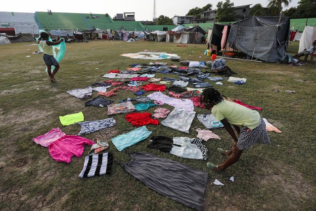 A child who was evacuated from her home looks at the clothes while waiting for them to dry, at a stadium used as a shelter in Les Cayes, Haiti, August 23, 2021. (Photo by Henry Romero/Reuters)