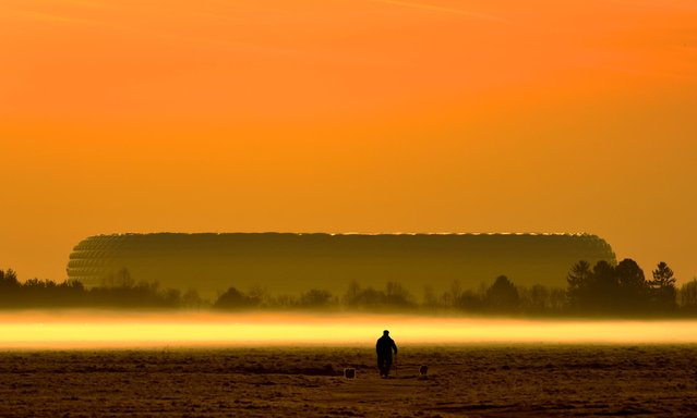 A man is silhouetted in front of the Allianz-Arena as he walks his dogs at sunrise in Munich, southern Germany, Friday, April 10, 2015. (Photo by Peter Kneffel/AP Photo/DPA)