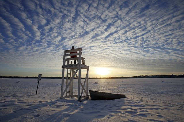 Jennifer Berry watches the sunset from a lifeguard chair at a beach on Lake Calhoun in Minneapolis, January 7, 2014. (Photo by Eric Miller/Reuters)