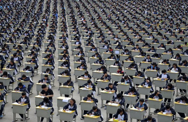 Students take an examination on an open-air playground at a high school in Yichuan, Shaanxi province April 11, 2015. More than 1,700 freshmen students took part in the exam on Saturday, which was the first attempt by the school to take it in open-air. The school said the reasons was due to the insufficient indoor space and also that it could be a test of the students' organizing capacity, local media reported. (Photo by Reuters/Stringer)