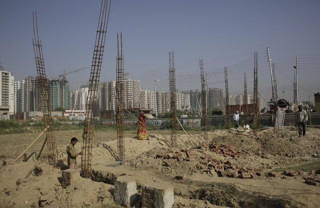 Indian workers work on a building being constructed on an agricultural land on Earth Day in New Delhi, India, Wednesday, April 22, 2015. The world marks Earth Day on April 22 to increase awareness and to promote practices for the sustainability and protection of the Earth's natural environment. (Photo by Altaf Qadri/AP Photo)