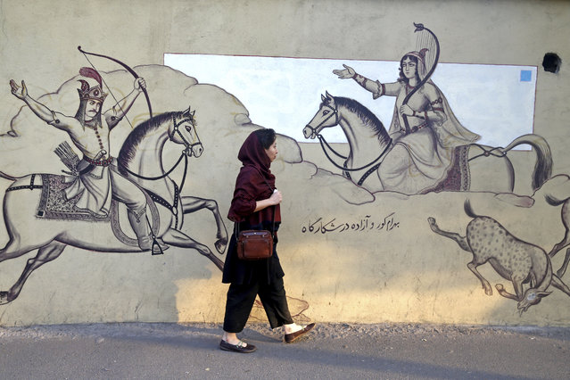 An Iranian woman walks past paintings of a Persian poetry in downtown Tehran, Iran, Monday, July 30, 2018. Iran's currency has dropped to a record low ahead of the imposition of renewed American sanctions, with many fearing prolonged economic suffering or possible civil unrest. (Photo by Ebrahim Noroozi/AP Photo)