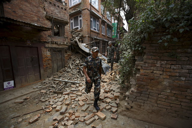 Nepalese army personnel walk next to the collapsed houses a day after an earthquake in Bhaktapur, Nepal April 26, 2015. (Photo by Navesh Chitrakar/Reuters)
