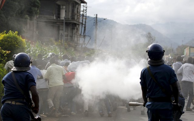 Riot police spray teargas on residents participating in street protests against the decision made by Burundi's ruling National Council for the Defence of Democracy-Forces for the Defence of Democracy (CNDD-FDD) party to allow President Pierre Nkurunziza to run for a third five-year term in office, in the capital Bujumbura, April 26, 2015. (Photo by Thomas Mukoya/Reuters)