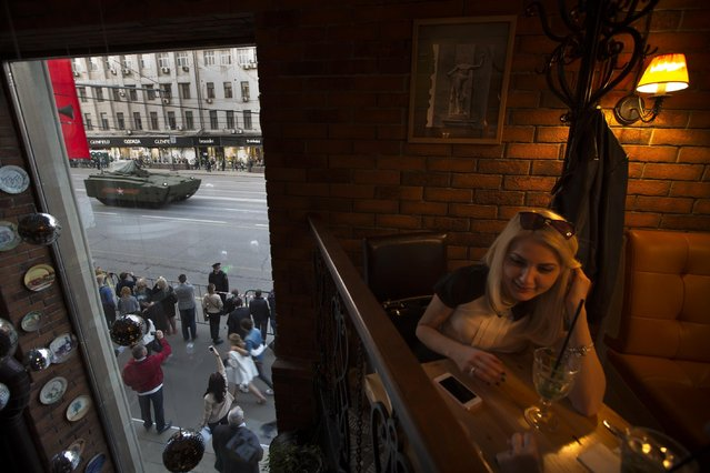A woman sits in a cafe as new Russian military vehicles make their way to Red Square during a rehearsal for the Victory Day military parade which will take place at Moscow's Red Square on May 9 to celebrate 70 years after the victory in WWII, in Moscow, Russia, Wednesday, April 29, 2015. (Photo by Alexander Zemlianichenko/AP Photo)