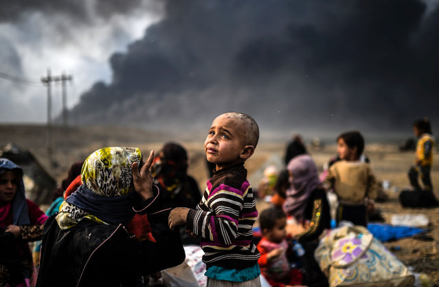 Iraqi families who were displaced by the ongoing operation by Iraqi forces against jihadistds of the Islamic State group to retake the city of Mosul, are seen gathering on an area near Qayyarah on October 24, 2016. The UN refugee agency is preparing to receive 150,000 Iraqis fleeing fighting around the Islamic State group-held city of Mosul within the next few days, its chief said. (Photo by Bulent Kilic/AFP Photo)