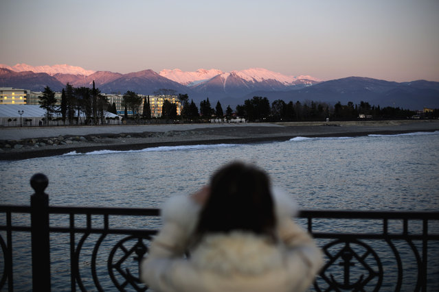 The Caucasus Mountains, site of the 2014 Winter Olympic outdoor snow sport and sliding track events, rise in the background as a woman takes a picture along the Black Sea outside the Olympic Park, Monday, February 3, 2014, in Sochi, Russia. (Photo by David Goldman/AP Photo)