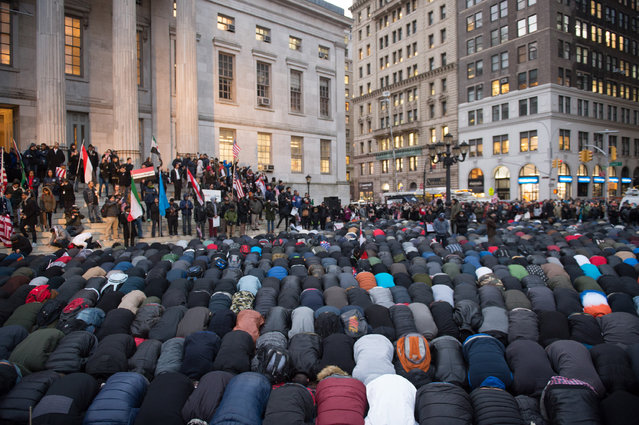 People gather for evening prayer at a rally at Brooklyn Borough Hall as Yemeni bodega and grocery-stores shut down to protest US President Donald Trump's Executive Order banning immigrants and refugees from seven Muslim-majority countries, including Yemen, on February 2, 2017 in New York. (Photo by Bryan R. Smith/AFP Photo)